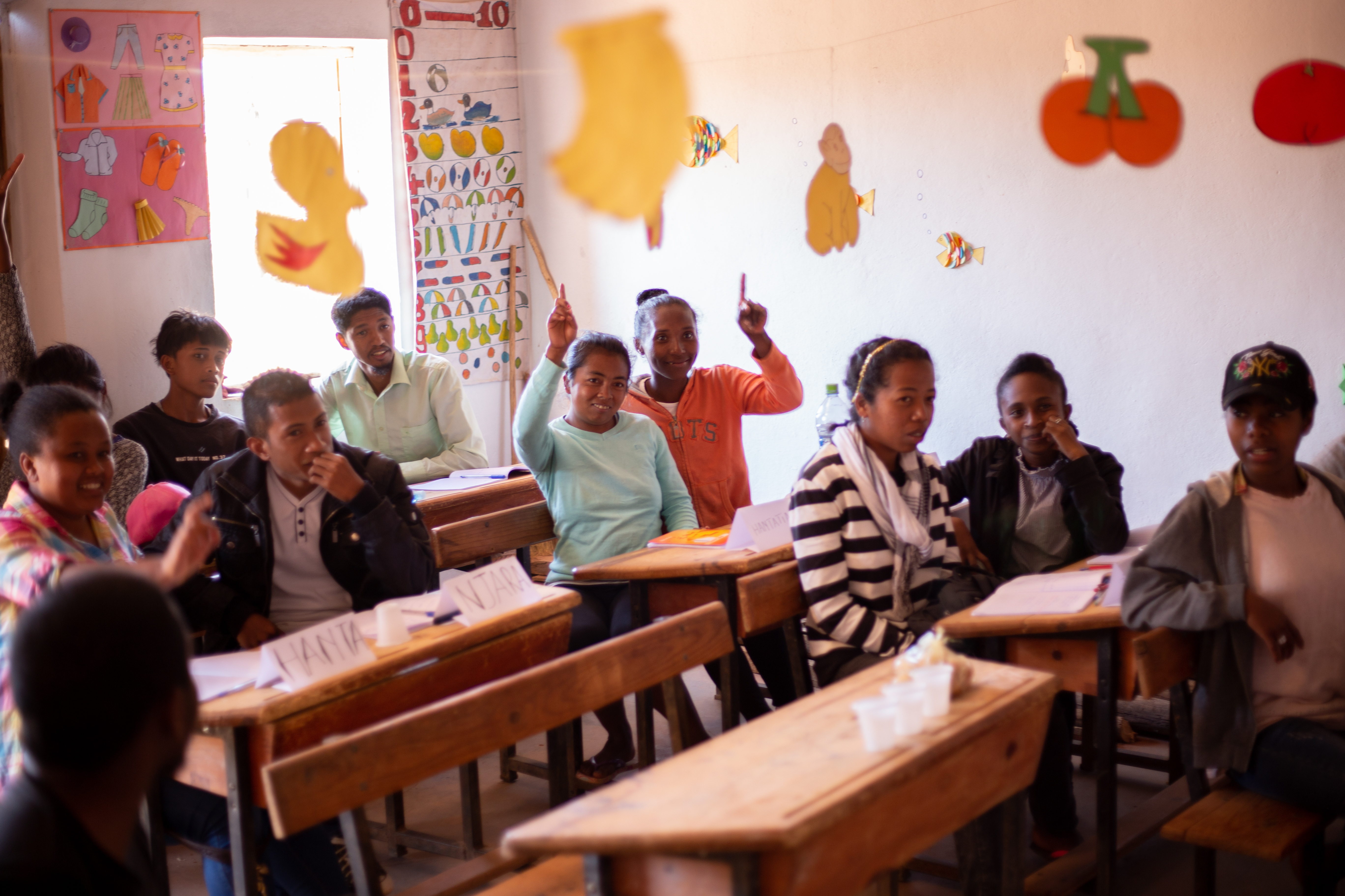 Eleven young people in a classroom setting. Two young women have their hands raised