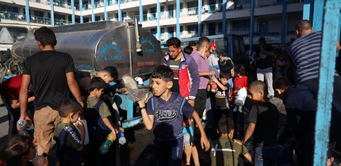 Children in Gaza collect water from truck