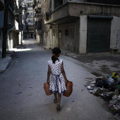Girl in Syria carries jerry cans