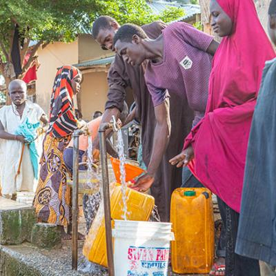 Nigerians access water at a public water point